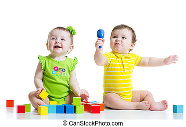 Two adorable babies playing with toys. Toddlers girl and boy sitting on floor. Isolated on white background.