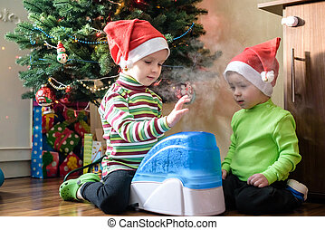 two adorable boys playing with working humidifier, waiting...
