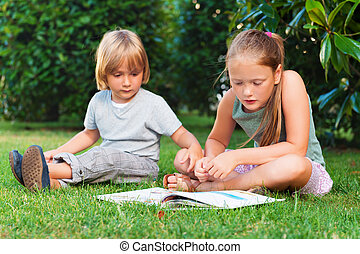 Two adorable kids, little boy and his sister reading a book in garden on a nice warm sunny day