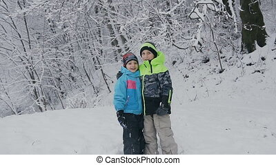 Two adorable little boys having fun together in beautiful winter park. Beautiful brothers playing fall down in a snow. Winter activities for kids