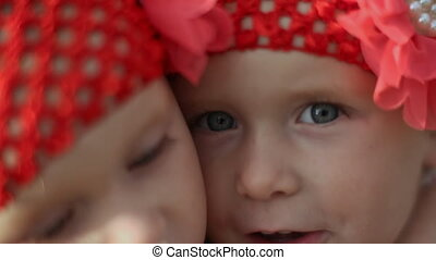 Two adorable little girls, twins eat bread in the fresh air. Together. Face close-up.