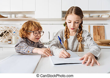 Two adorable siblings studying together