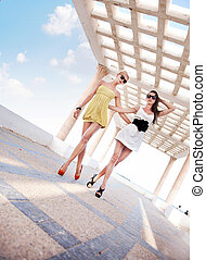 Two adorable women walking in a sunny day