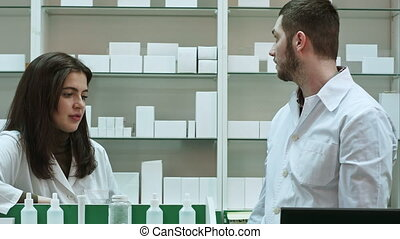 Two adult pharmacists having conflict, discussing problems at pharmacy