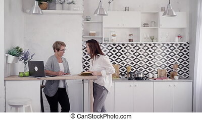 Two adult woman spending free time at home and talking on...