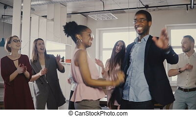 Two African American colleagues dancing together at casual...