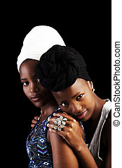Two African American Sisters In Headscarfs On Dark Background
