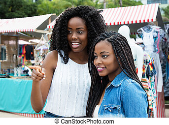 Two african american woman shopping at market