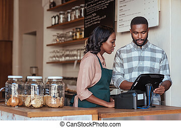 Two young African entrepreneurs working together on the terminal at the checkout counter of their trendy cafe