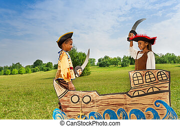 Two African kids as pirates dueling with swords