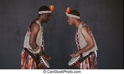 Two African mans dancing and drumming