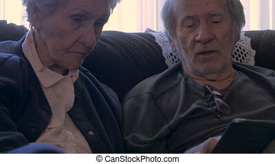 Two aging seniors talk while holding a mobile tablet - dolly...