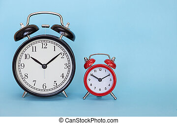 Two alarm clocks on a color background with free space for text