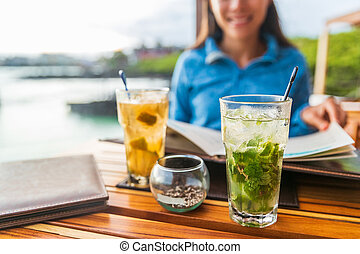 Two alcoholic cocktails at beach restaurant outside on dining table. Woman and closeup of drink mojito cocktail