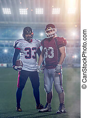 Two American football players standing  on the field