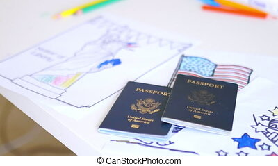 American passports above coloring pages of statue of Liberty, the Capitol, and the American flag. Passports above coloring pages on desk. American patriotic symbols