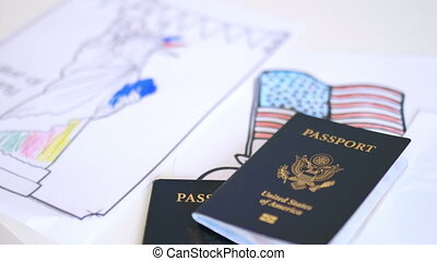 American passports above coloring pages of the American flag and the Statue of Liberty. Passports above coloring pages on desk. American patriotic symbols