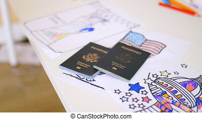 American passports above images of the American flag, the Statue of Liberty, and the Capitol. Passports above coloring pages on desk. American patriotic symbols