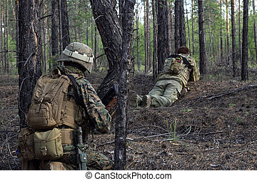 Two american soldiers are on a stakeout in the summer forest, waiting for the enemy, active military game airsoft