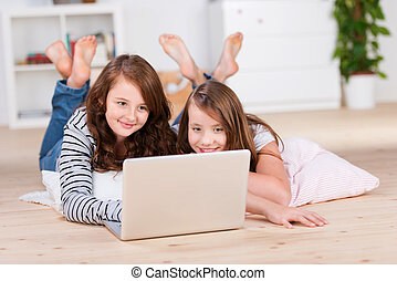 Two amused young teenage girls using a laptop