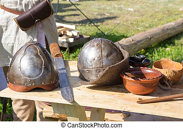 two ancient helmet and sword on wooden table
