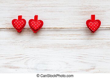 Two and one red polka-dot hearts on clothespins at wooden border. Valentine's day background with hearts