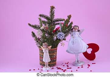 Two angel figurines on pink background