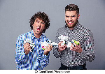 Two angry men with crumpled paper