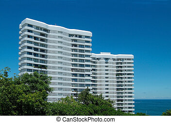 Two apartment-buildings by the sea - Two tall, white ...