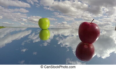 two apple on mirror and clouds motion. Time concept...