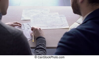Two architects are working together on building blueprints on the table.