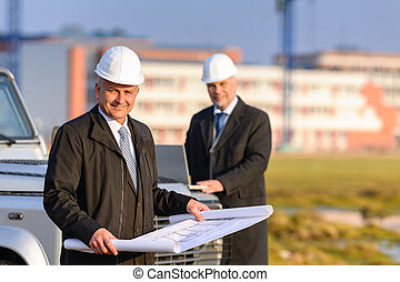 Two architects at construction site review plans