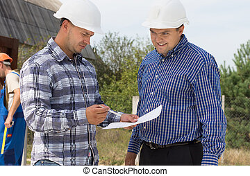 Two architects checking specifications