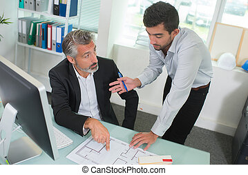 two architects discussing blueprints in the office