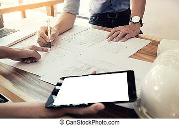 Two Architects engineer discussing  data working and tablet, laptop with blueprint - Closeup on hands and project print