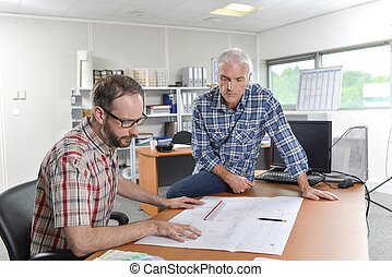 Two architects gathered around plans