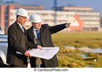 Two architects man point at construction site