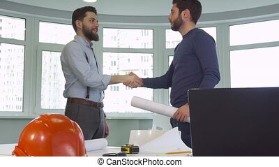 Two architects shake hands at the office - Two young male...
