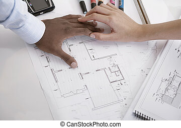 Two architects with blueprints (focus on hands)