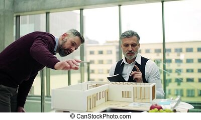 Two architects with model of a house in office, talking. -...