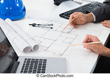 Two Architects Working On Blueprint