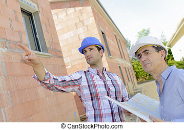 Two architects working on site