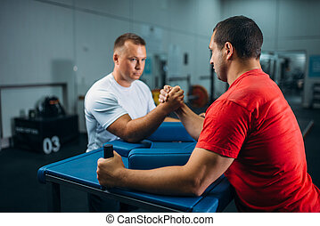 Two arm wrestlers at the table with pins, training