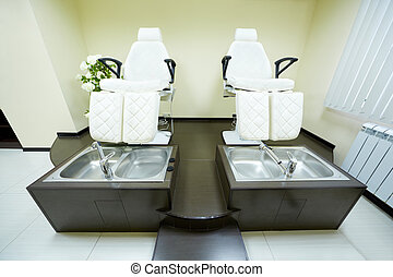 Two armchairs and bathtubs in the pedicure cabinet in the beauty salon.