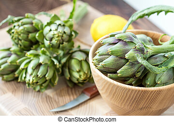 Two artichoke bouquets on kitchen table among some kitchen items