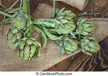 Two artichoke bouquets on sackcloth on wooden background. Top view.