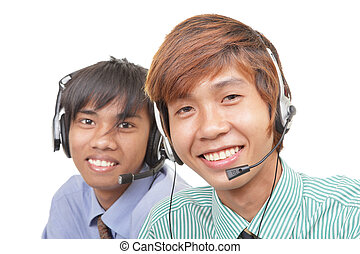 Two Asian call center agents or customer care...