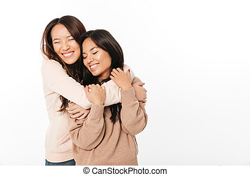 Two asian cute ladies sisters standing isolated
