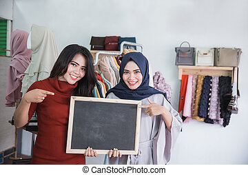 two asian fashion store owner with blank board