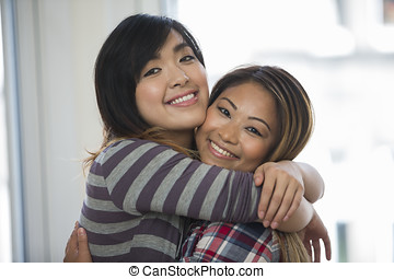 Two Asian female friends at home.